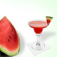 Frozen Watermelon Margarita en una copa de margarita decorado con un pedazo de sandía y con una pizca de azúcar o sal.
