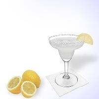 Margarita en una copa de margarita decorado con una rodaja de limón y con una pizca de azúcar o sal.