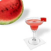Watermelon Margarita en una copa de margarita decorado con un pedazo de sandía y con una pizca de azúcar o sal.
