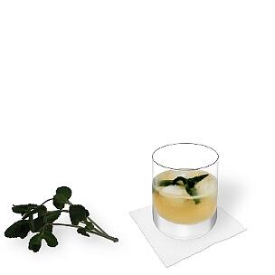 Whisky Sour servido en un vaso de whisky con decoración de menta, es la manera más común de presentar esta bebida sabrosa.
